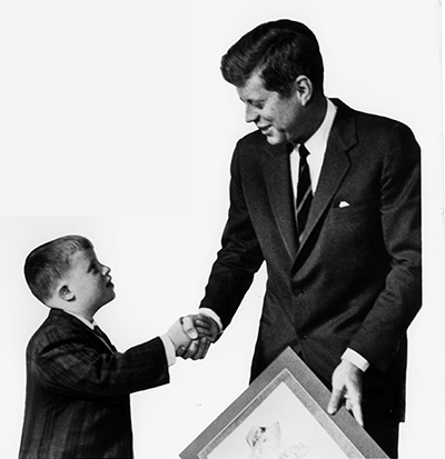 Photo of John F. Kennedy shaking hands with a child