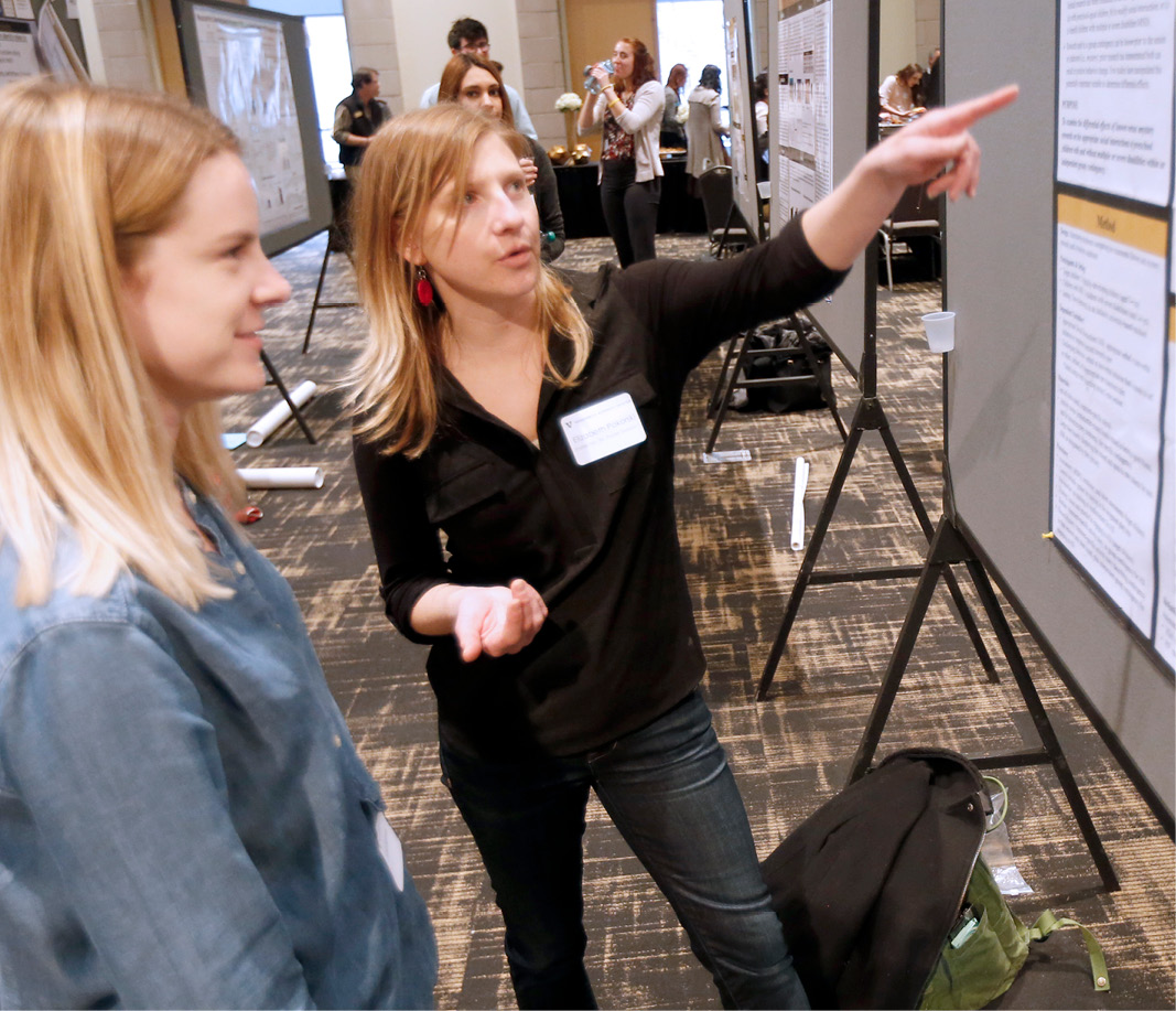 Two women talking and looking at poster at Science Day