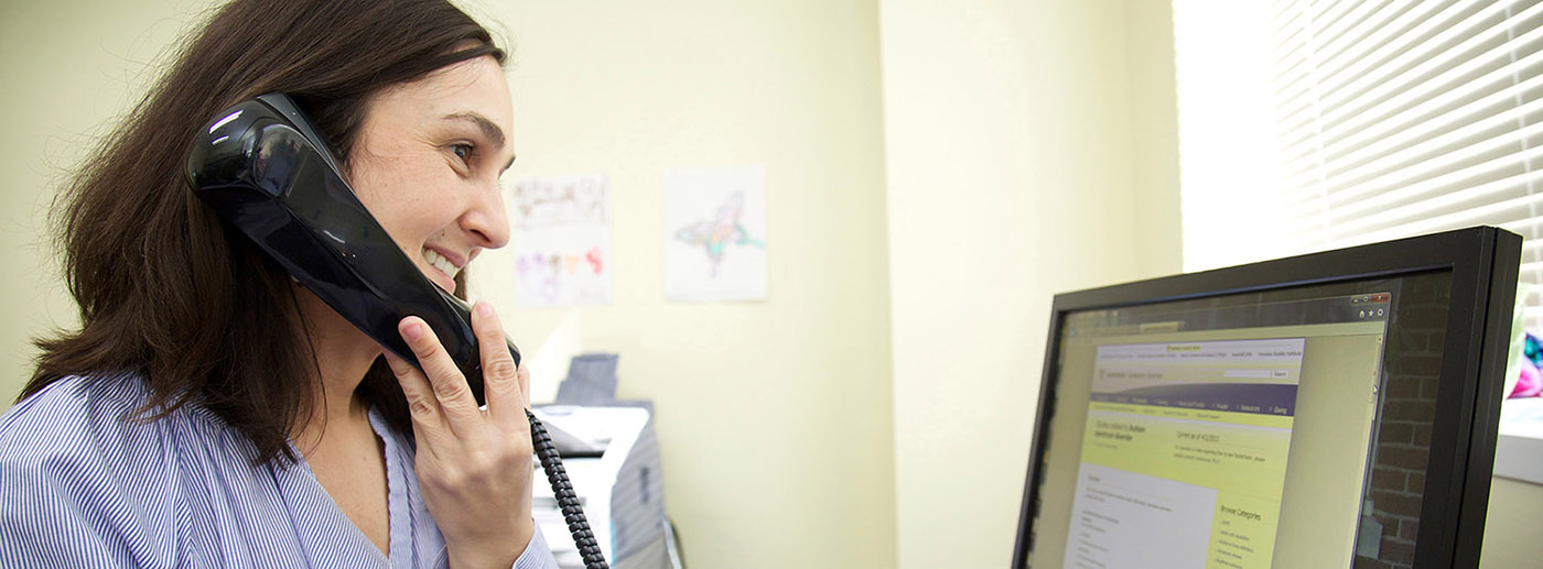 <p>A woman answering the Autism Resource phone line</p>